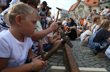 Grupa dzecie na tarnogórskim rynku uderza młotkami w szynę kolejową. W tle kościół ewangelicki.