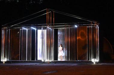 Aktorka w zakrwawionej białej sukience w metalowej scenografii na kółkach