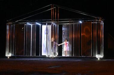 Metalowa podświetlona scena. Dziewczynka w zakrwawionej białej sukience trzyma za rękę aktora przebranego za mysz.