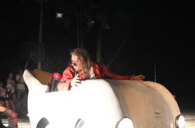 Aktor w czerwonym kostiumie siedzi w białym małym samochodzie. Za plecami ma czerwoną walizkę.