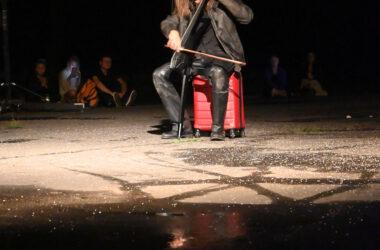 Aktor siedzący na walizce i grający na instrumencie