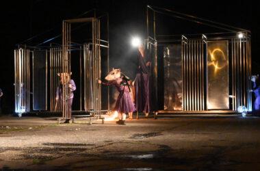 Na tle metalowej podświetlonej sceny dwóch aktorów przebranych za myszy w fioletowych strojach. W tle aktor na szczudłach w fioletowej sukni.