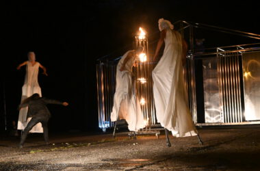 3 aktorów na szczudłach w białych długich sukniach z workami na głowie