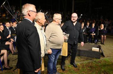 Trzech mężczyzn z Aleksandrem Konigiem na tle orkiestry