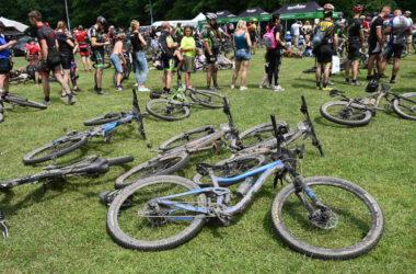 Ubłocone rowery położone na trawie na tle uczestników maratonu