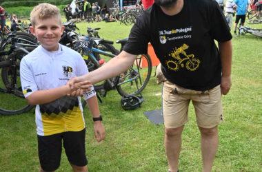 Oficer rowerowy gratulujący chłopcu udziału w maratonie