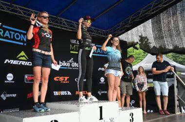 3 kobiety na podium z medalami uniesionymi w górę