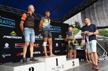 2 mężczyzn na podium, 1 z dzieckiem na rękach obok oraz mężczyzna niosący medal