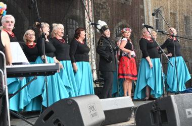Na scenie studentki Tarnogórskiego Uniwersytetu Trzeciego Wieku w niebieskich spódnicach i czarnych bluzkach. Po środku kobieta w stroju ludowym i w stroju górnika.