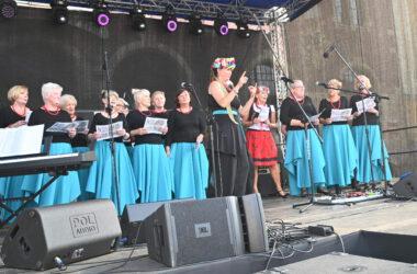 Na scenie studentki Tarnogórskiego Uniwersytetu Trzeciego Wieku w niebieskich spódnicach i czarnych bluzkach. Po środku kobieta w stroju ludowym i dyrygentka w ludowym wianku.