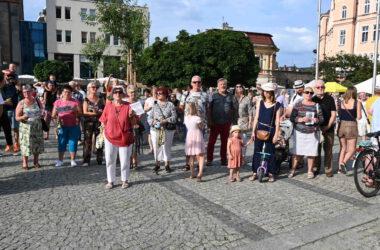 Publiczność zgromadzona na rynku w Tarnowskich Górach na tle budynków.