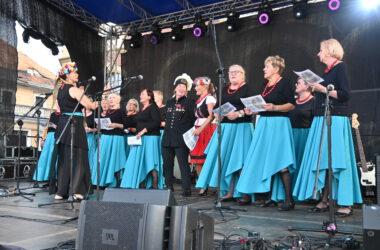Na scenie studentki Tarnogórskiego Uniwersytetu Trzeciego Wieku w niebieskich spódnicach i czarnych bluzkach. Po środku kobieta w stroju ludowym i w stroju górnika. Z lewej strony dyrygentka w ludowym wianku.