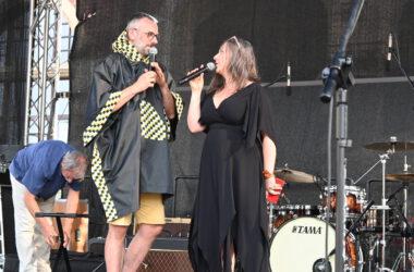 Na scenie mężczyzna w tarnogórskiej pelerynie przeciwdeszczowej z kobietą w czarnej sukience, prowadzą pokaz mody.