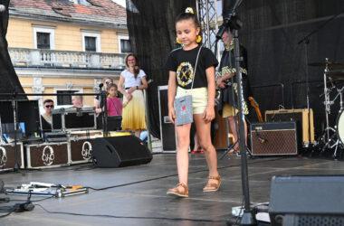 Na scenie dziewczynka w czarnej koszulce i żółtych spodenkach z filcową szarą torebką.