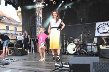 Na scenie uśmiechnięta mama w żółtej spódniczce za kolana z córeczką w różowej koszulce i z torebką w tarnogórską kratę.
