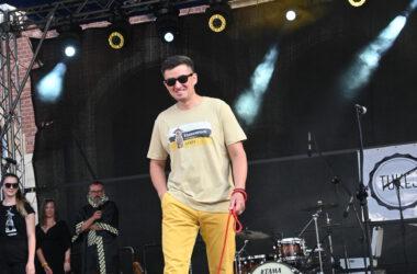 Na scenie uśmiechnięty mężczyzna w żółtych spodniach z psem na czerwonej smyczy w chuście w tarnogórską kratę.