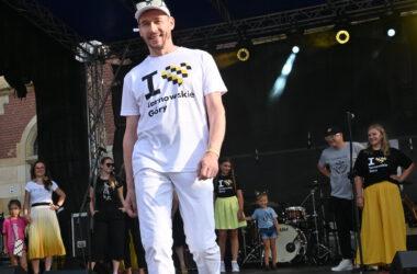 Na scenie na tle uczestników pokazu mody mężczyzna w czapce z daszkiem i białym stroju z logo I love Tarnowskie gÓRY.