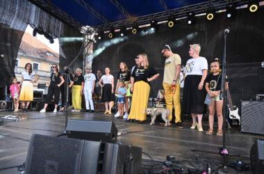 Grupa uczestników pokazu mody tarnogórskiej na scenie z psem.