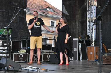 Na scenie kobieta i mężczyzna w koszulce z napisem I love Tarnowskie Góry, zapowiadają pokaz mody.