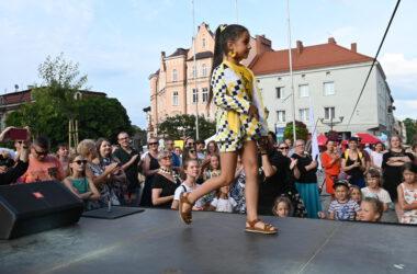 Na scenie przed publicznością dziewczynka w stroju w tarnogórską kratę