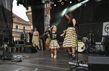Na scenie na pierwszym planie mama z córeczką w strojach w tarnogórską kratę. W tle z lewej strony sceny 4 osoby.