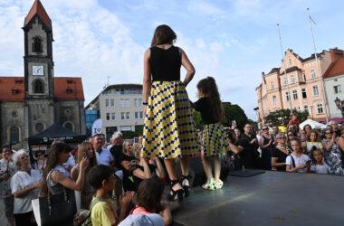 Na scenie przed publicznością kobieta z córką w spódniczkach w tarnogórską kratę