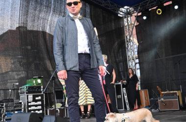 Na scenie podczas pokazu mody mężczyzna z psem w chustce w tarnogórską kratę