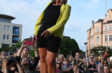 Na scenie przed publicznością kobieta w kapeluszu, czarnym kombinezonie i żółtym swetrze