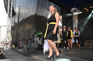 Na scenie kobieta w czarnej sukience z żółtym paskiem