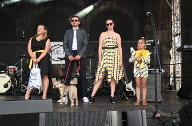 Mężczyzna z psem, 2 kobiety i dziewczynka z pluszową kredką w dłoniach na scenie w trakcie pokazu mody
