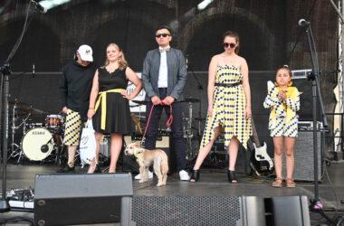Na scenie 2 kobiety, dziewczynka z dużą pluszową kredką i dwóch mężczyzn w tym jeden z psem. Wszyscy w strojach z tarnogórską kratką.