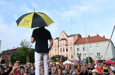 Mężczyzna z tarnogórskim parasolem przed zgromadzoną publicznością na tarnogórskim rynku