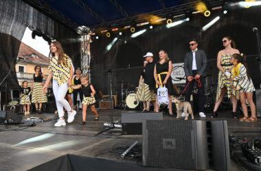 Grupa osób na scenie w tarnogórskich strojach, wśród nich mężczyzna z psem.