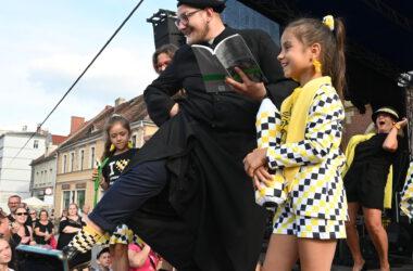 Na scenie dwie dziewczynki w tarnogórskich strojach i ksiądz w sutannie, berecie i tarnogórskich skarpetkach trzyma książkę.