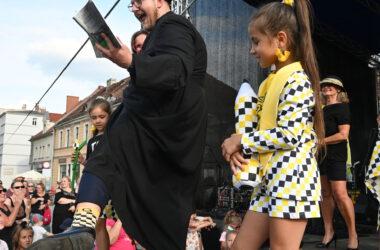 Na scenie dziewczynka z pluszową kredką w tarnogórską kratę i ksiądz w sutannie i tarnogórskich skarpetkach