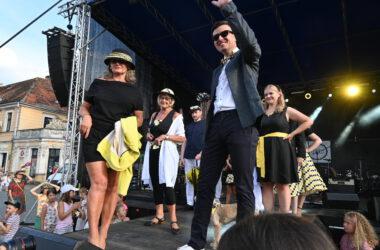 Na pierwszym planie na scenie mężczyzna w marynarce z uniesioną w górę ręką i kobieta w kapeluszu na tle uczestników pokazu mody