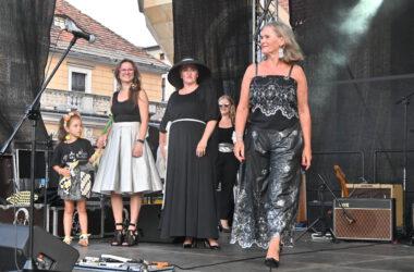 3 kobiety i dziewczynka na scenie w trakcie pokazu mody
