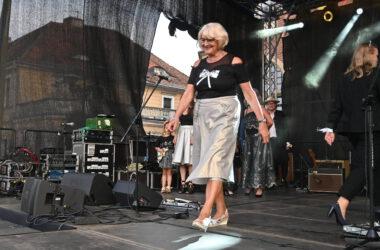 Kobieta w srebrnej spódnicy i bluzce z kokardą na scenie podczas pokazu mody