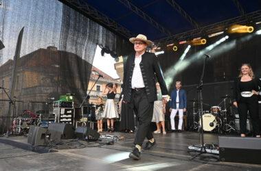 Mężczyzna w słomkowym kapeluszu i czarnym stroju na scenie w trakcie pokazu mody