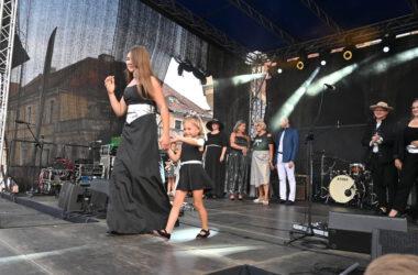 Dziewczyna z dzieckiem w czarnej sukience ze srebrnym paskiem, na scenie podczas pokazu mody.