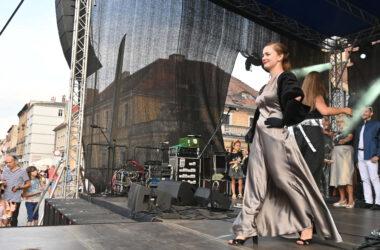 Kobieta w srebrnej sukience na scenie podczas pokazu mody.