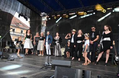 13 osób na scenie podczas pokazu mody