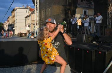 Mężczyzna tańczący z córeczką na rękach przed sceną