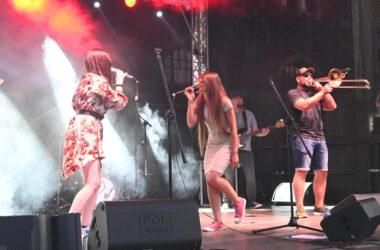 2 Wokalistki zespołu Tukej śpiewają do mikrofonów z muzykami na scenie