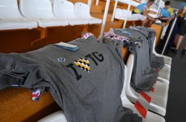 Szare koszulki na krzesłach trybun Hali Sportowej.