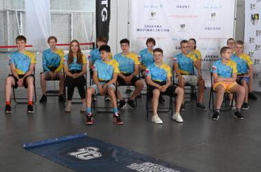 Zawodnicy klubu pływackiego w sportowych strojach, siedzą na krzesłach w Hali Sportowej.