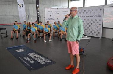 Trener z mikrofonem a w tle zawodnicy klubu pływackiego.