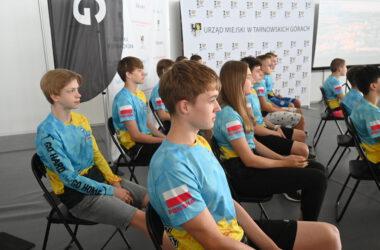 Zawodnicy klubu pływackiego siedzą na krzesłach w Hali Sportowej.