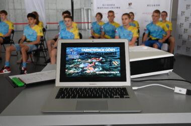 Otwarty laptop w tle zawodnicy tarnogórskiego klubu pływackiego.
