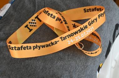 Pomarańczowa smycz reklamująca sztafetę pływacką.